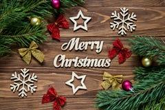 Ramos do pinho com bolas do Natal Decoração agradável do Natal com curvas, flocos de neve e estrelas da fita no de madeira Imagens de Stock