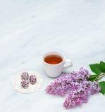 Ramos lilás da flor, copo do chá e bolas da felicidade em Carrara miliampère Imagem de Stock Royalty Free