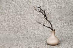 Ramos secos escuros e claros em um jarro no fundo da lona - ainda vida da argila no estilo rústico foto de stock royalty free
