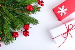 Ramos spruce verdes decorados com bagas e caixas de presente em um fundo branco Anos novos, decoração do Natal Tema festivo Fotografia de Stock