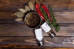 Ramoscelli dei rosmarini e del peperoncino con le foglie dell'alloro ed i piselli neri del pepe in barattolo, latte dell'agitator Immagini Stock Libere da Diritti