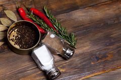 Ramoscelli dei rosmarini e del peperoncino con le foglie dell'alloro ed i piselli neri del pepe in barattolo, latte dell'agitator Fotografia Stock Libera da Diritti