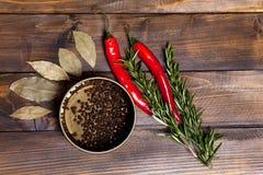 Ramoscelli dei rosmarini e del peperoncino con le foglie dell'alloro ed i piselli neri del pepe in un barattolo su fondo di legno Immagini Stock