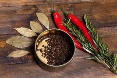 Ramoscelli dei rosmarini e del peperoncino con le foglie dell'alloro ed i piselli neri del pepe in un barattolo su fondo di legno Fotografia Stock