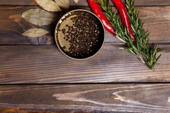 Ramoscelli dei rosmarini e del peperoncino con le foglie dell'alloro ed i piselli neri del pepe in un barattolo su fondo di legno Fotografia Stock Libera da Diritti