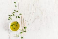 Ramoscelli di timo e di olio d'oliva su un fondo misero bianco, spac Immagini Stock
