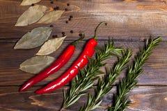 Ramoscelli rossi dei rosmarini e del peperoncino con le foglie dell'alloro su fondo di legno Immagini Stock Libere da Diritti