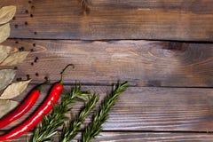 Ramoscelli rossi dei rosmarini e del peperoncino con le foglie dell'alloro su fondo di legno Immagine Stock Libera da Diritti