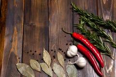 Ramoscelli rossi dei rosmarini e del peperoncino con le foglie dell'alloro e le teste bianche dell'aglio su fondo di legno Fotografie Stock Libere da Diritti