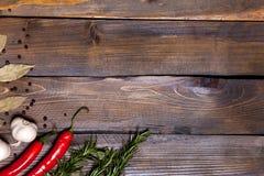 Ramoscelli rossi dei rosmarini e del peperoncino con le foglie dell'alloro e le teste bianche dell'aglio su fondo di legno Immagine Stock Libera da Diritti