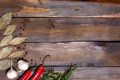 Ramoscelli rossi dei rosmarini e del peperoncino con le foglie dell'alloro e le teste bianche dell'aglio su fondo di legno Fotografie Stock
