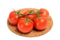 Ramoscello del pomodoro rosso con le gocce di acqua su una base del sughero Fotografie Stock Libere da Diritti