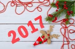 Ramoscello dell'abete del nuovo anno e bacche rosse su un fondo di legno Fotografia Stock