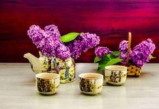 Ramoscello lilla del lillà della teiera del tè verde del tè Fotografie Stock