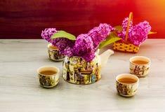 Ramoscello lilla del lillà della teiera del tè verde del tè Fotografia Stock