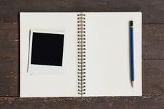 Ramowa fotografia i brąz książka na drewno stole Obrazy Stock