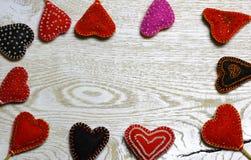 Ramowa granica Handmade odczuwani serca na lekkim drewnianym tle Zdjęcia Royalty Free