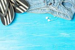 Ramowe eleganckie kapci cajgów słuchawki na błękitnym drewnianym tle, copyspace dla teksta, wakacje obraz royalty free