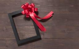 Ramowy obrazka i czerwieni faborek jest na drewnianym tle z e Obrazy Royalty Free