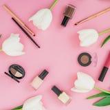 Ramowy skład z tulipanów kosmetykami na różowym tle i kwiatami Odgórny widok Mieszkania nieatutowy domowy kobiecy biurko Zdjęcia Stock
