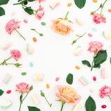Ramowy wzór z różami kwitnie, pączki, liście i marshmallows z cukierkiem na białym tle, Mieszkanie nieatutowy, odgórny widok Obraz Stock