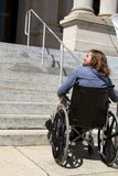 Ramp Building Access. Disabled man in wheelchair looks for a ramp to gain access to a public building entrance Stock Image