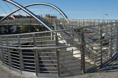 Ramp and steps. The steel structure of a bridge with ramp and stair access and metal railings with a blue sky in the background Royalty Free Stock Image