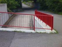 Rampa y escalera al aire libre con la verja roja Fotografía de archivo