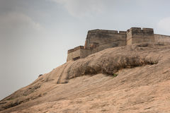 Rampart of historic Dindigul Rock Fort. Dindigul, India - October 23, 2013: Brown-beige boulder with the ramparts of the historic Dindigul Rock fort under light stock photos