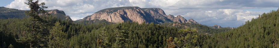 Rampart rising panorama 2. A mighty granite rampart rises out of the mountains and forest of central New Mexico in this true panorama Stock Image