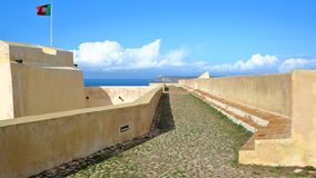 The ramparts of Sagres Fortress Fortaleza with Cabo de Sao Vicente St Vincent Cape lighthouse in the background, Sagres, Algar royalty free stock photo