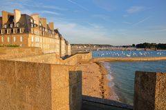 The ramparts of the walled city of Saint Malo at sunset, with the Mole beach and the harbor in the background, Saint Malo royalty free stock photo