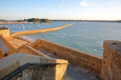 The ramparts of the walled city of Saint Malo at sunset, with the pier Mole des Noires and the harbor in the background, Saint M stock images