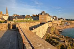 The ramparts of the walled city at sunset, with Saint Vincent Cathedral in the background and the Bon Secours beach on the right s stock photography