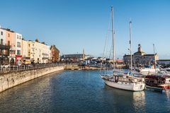 Ramsgate, Kent, UK shop fronts and marina. RAMSGATE, ENGLAND - NOV 23 2017.  Buildings  and boats in and around the marina in the winter evening sunshine. The Stock Image
