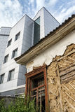 Ramshackle dilapidated abandoned old house and modern new building Stock Images