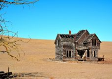 Ramshackle house on barren hillside Stock Images
