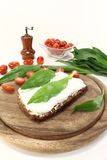 Ramson bread. Slice of bread with cottage cheese, ramson and chopped tomatoes Stock Photos