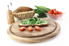 Ramson bread. With butter, fresh ramson and tomatoes on a light background Stock Image