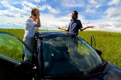 Ran Out Of Gas?. Couple on each side of a car out of commission.  Girl is upset; guy doesn't seem to care Stock Photography