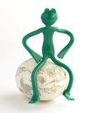 Rana del juguete que se sienta en una roca Foto de archivo libre de regalías