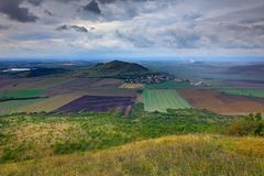Rana Hill, na montanha de Ceske Stredohori, República Checa Monte com nuvens Paisagem bonita da manhã Vila abaixo do monte La fotografia de stock royalty free