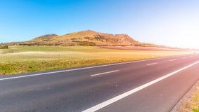 Rana Mountain und Asphaltstraße nahe Louny in den zentralen böhmischen Hochländern am sonnigen Sommertag, Tschechische Republik stockfotos
