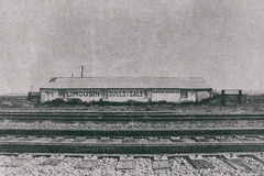 Ranch Building and Pens across Railroad Tracks. With Limousin Bulls for Sale printed on the side. Photographed in black and white in far West Texas Stock Photography