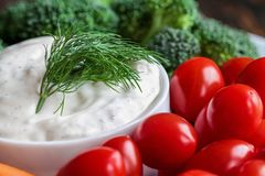Ranch Dressing with a Fresh Dill Sprig. Homemade buttermilk ranch salad dressing with dill served with cherry tomatoes, baby carrots and broccoli, over a rustic royalty free stock photography
