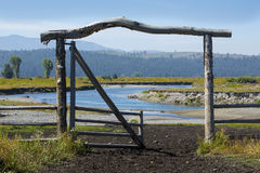 Ranch entry gate in pasture, bank of Buffalo Fork River, Wyoming Stock Photo
