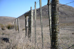 Ranch fence post with barbed wire. A fence post on a cattle ranch, with hills in the distance royalty free stock photos