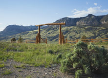 Ranch gate below Absaroka mountains in Wyoming. A wood ranch gate below cliffs of the Absraoka mountains in Wyoming Stock Photo