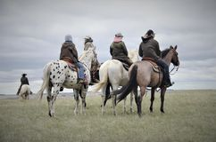 Ranch horses with riders in pasture royalty free stock photo
