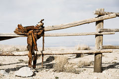 Ranch - saddle on fence. Ranch scene - saddle on rural fence, vintage worn saddle in the dry and barren countryside stock image